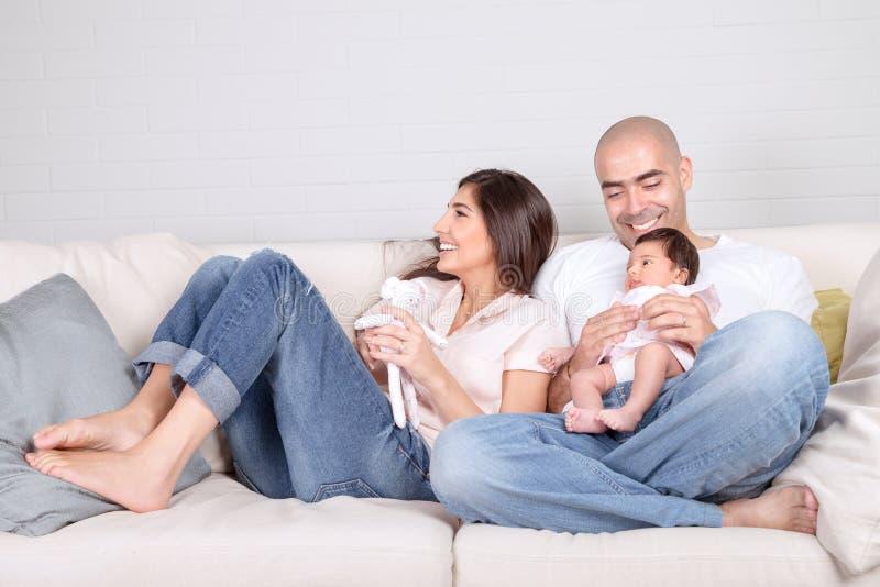Pais novos com bebê pequeno em casa foto de stock royalty free