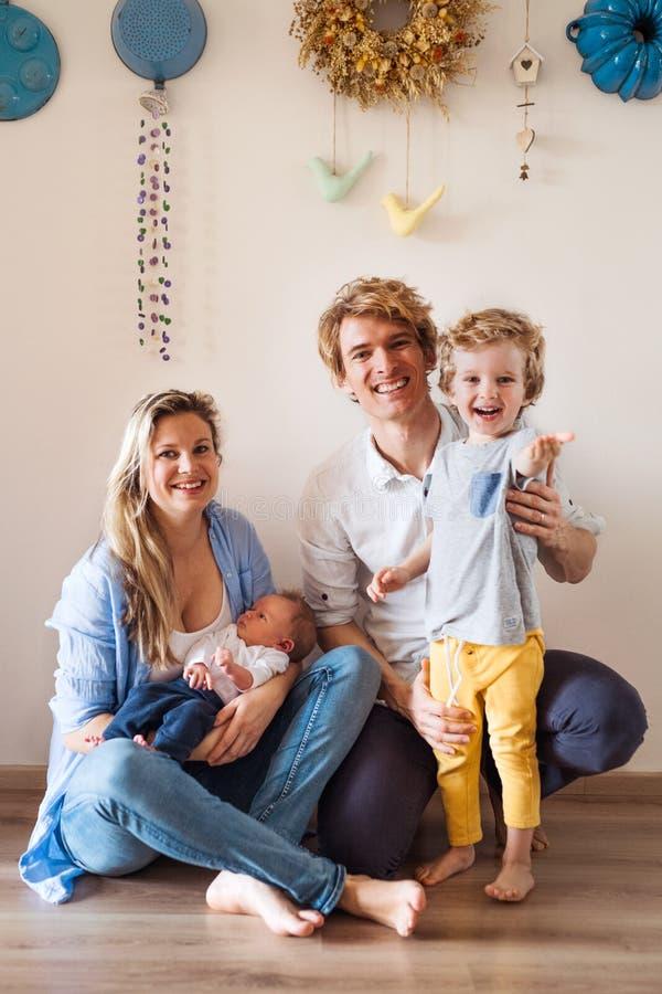 Pais novos com beb? rec?m-nascido e o filho pequeno da crian?a em casa imagem de stock