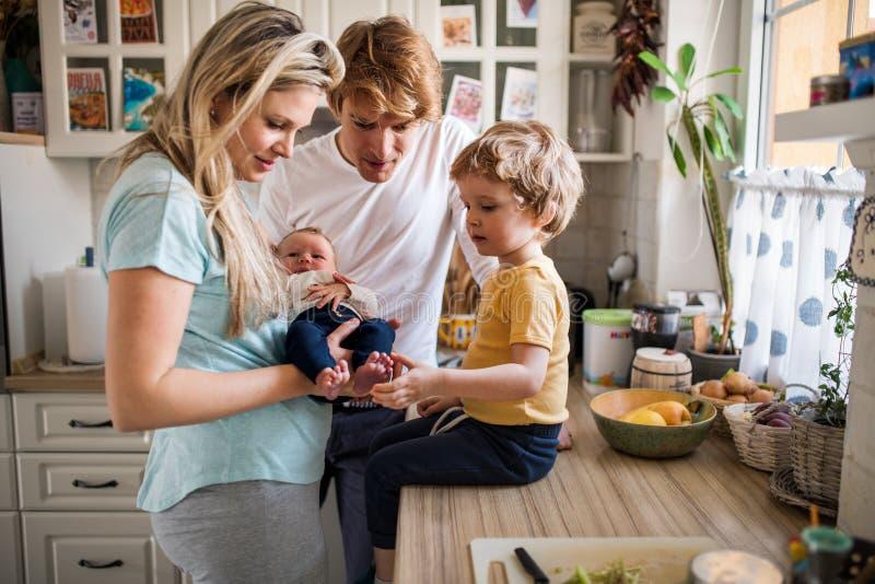 Pais novos com beb? rec?m-nascido e o filho pequeno da crian?a em casa imagens de stock royalty free