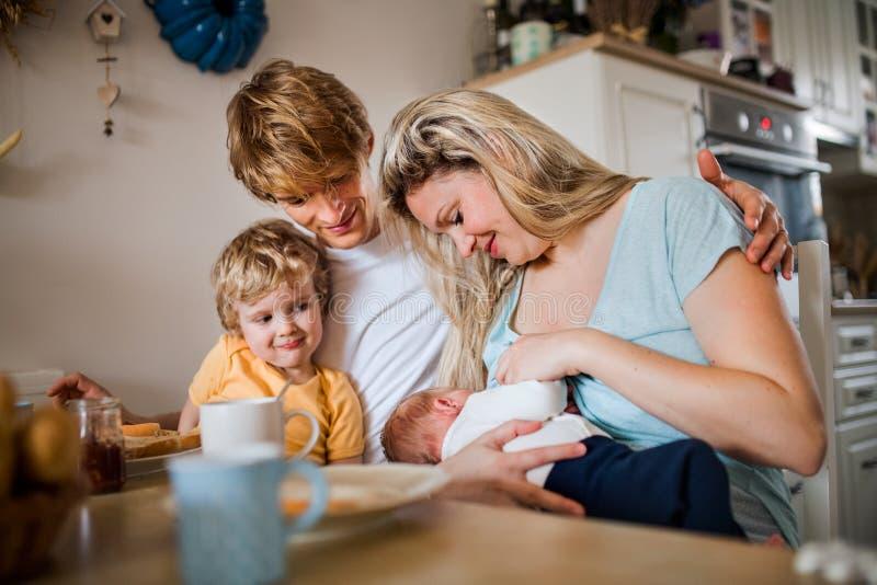 Pais novos com beb? rec?m-nascido e o filho pequeno da crian?a em casa fotografia de stock royalty free