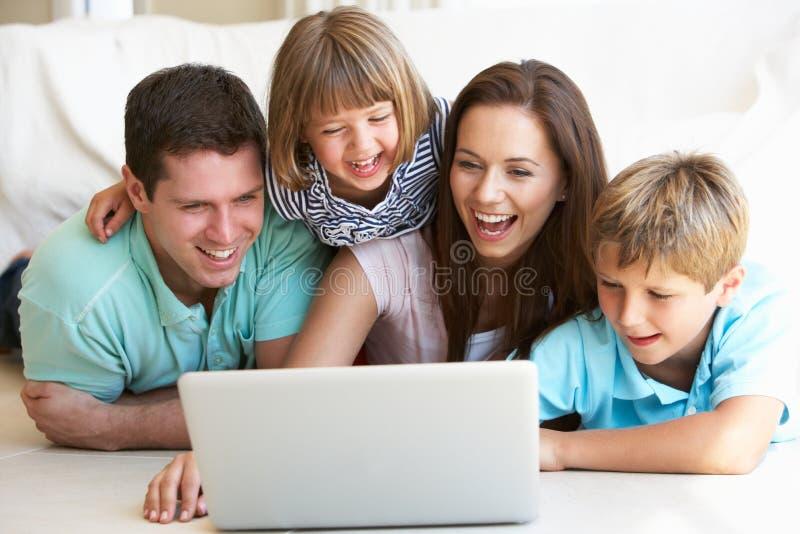 Pais novos, com crianças, no computador portátil