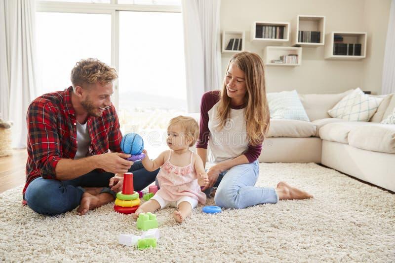 Pais novos e filha da criança que joga na sala de estar foto de stock