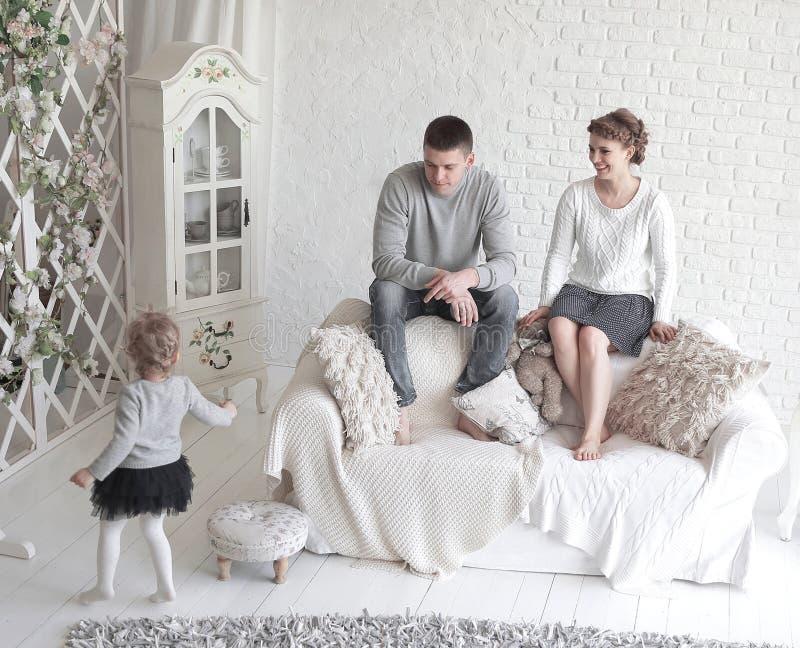 Pais novos e seus sorrisos pequenos bonitos da filha, sentando-se com seu pouco cão no sofá em casa fotografia de stock royalty free