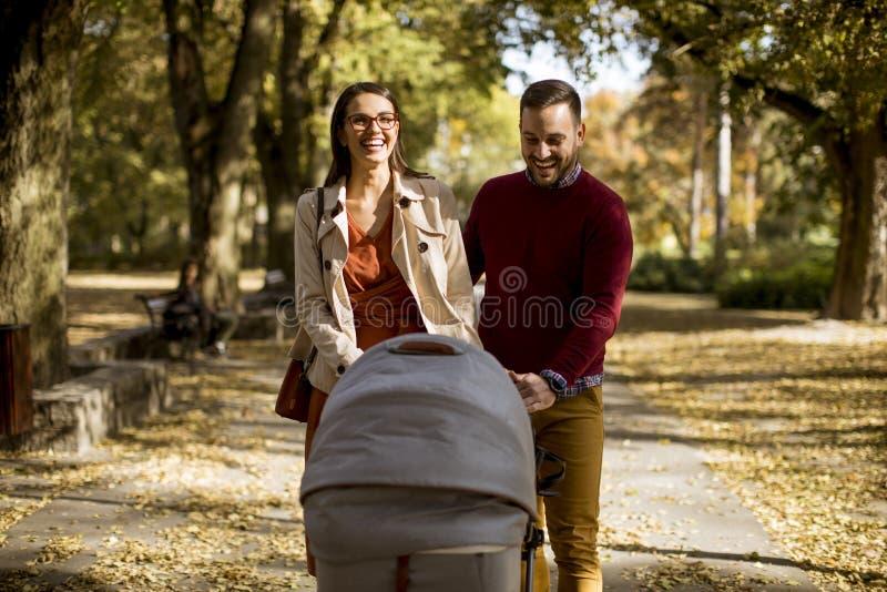 Pais novos felizes que andam no parque e que conduzem um bebê nos vagabundos fotografia de stock royalty free
