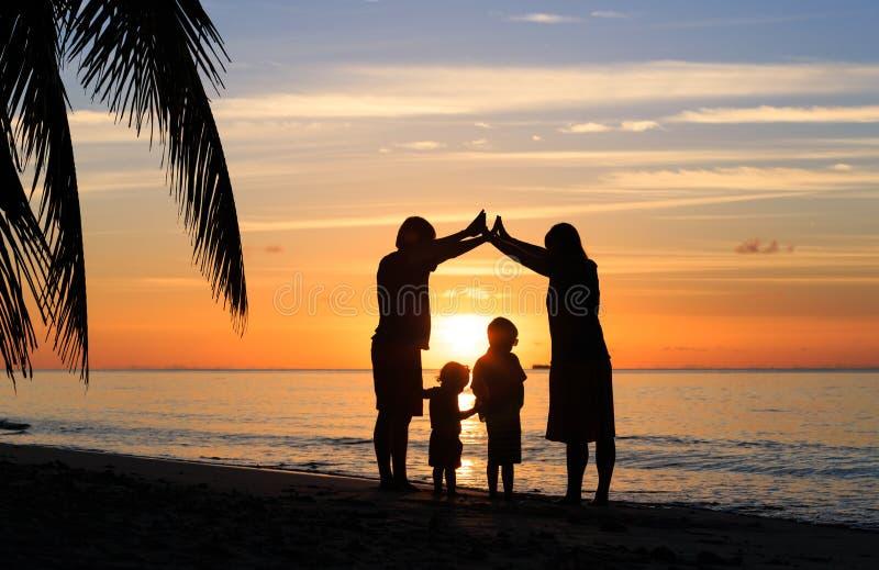 Pais novos felizes que fazem em casa para crianças no por do sol foto de stock royalty free