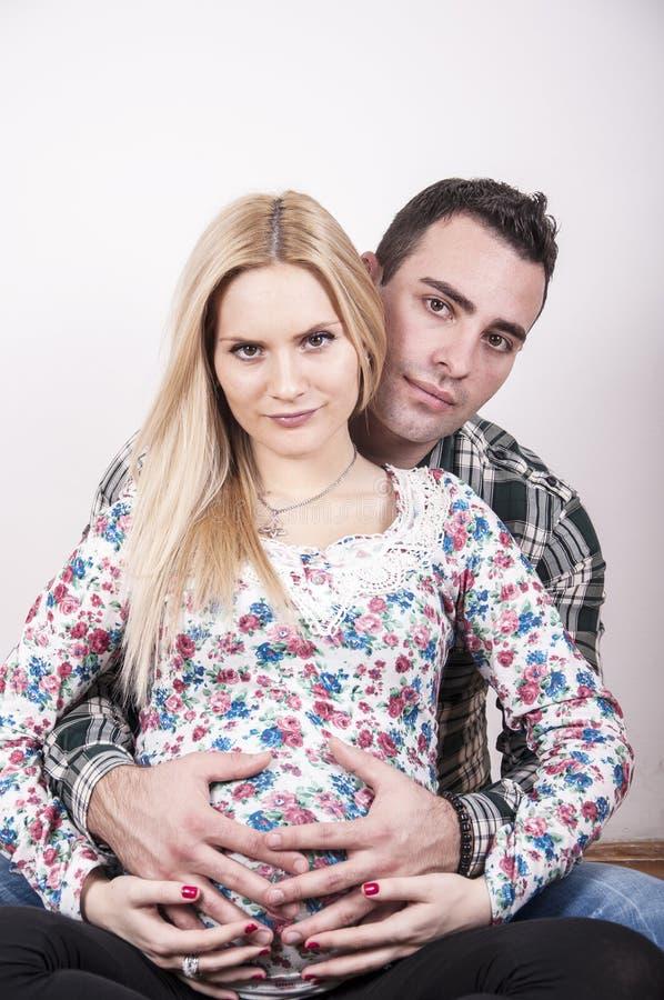 Pais novos que abraçam a barriga imagens de stock royalty free