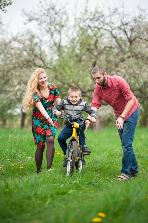 Pais novos que ensinam seu filho montar uma bicicleta fotografia de stock royalty free