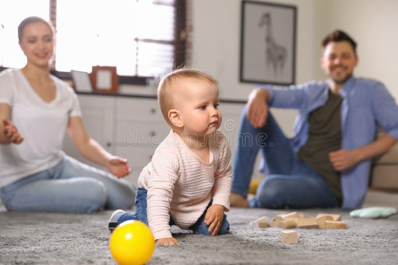 Pais observando seu bebê rastejar no chão imagem de stock