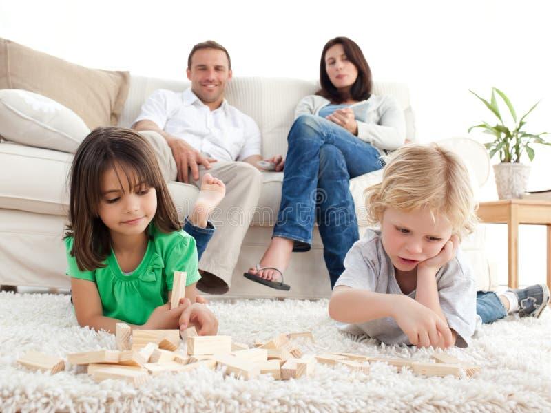 Pais orgulhosos que olham seu jogo das crianças foto de stock