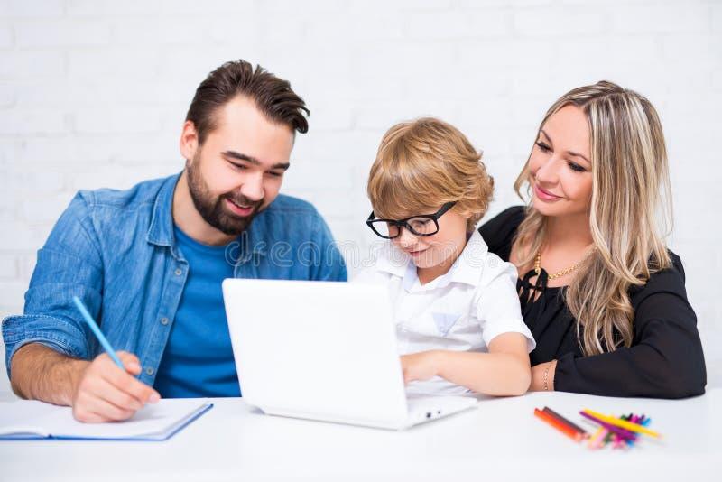 Pais que ajudam ao menino de escola pequeno bonito feliz que faz os trabalhos de casa a fotos de stock royalty free