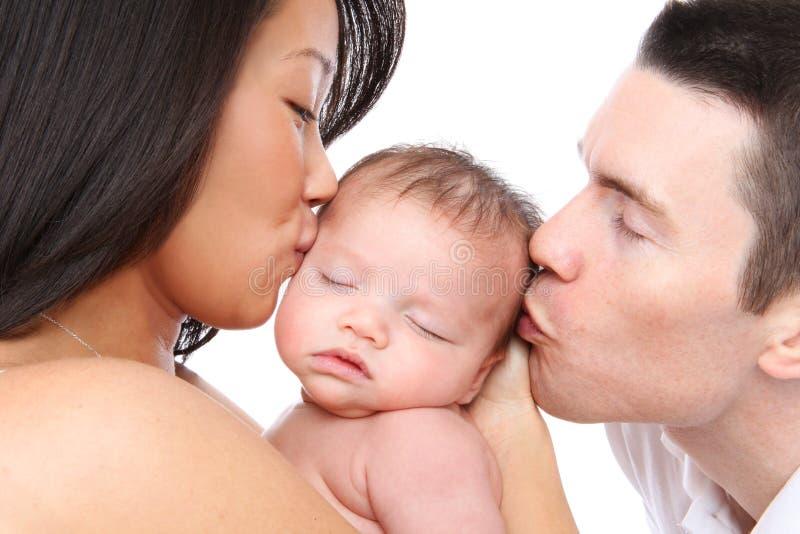 Pais que beijam o bebê imagens de stock