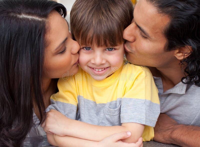 Pais que beijam seu filho foto de stock
