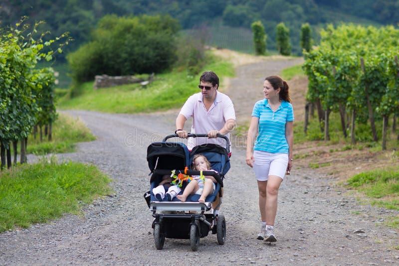 Pais que caminham com carrinho de criança dobro fotografia de stock royalty free