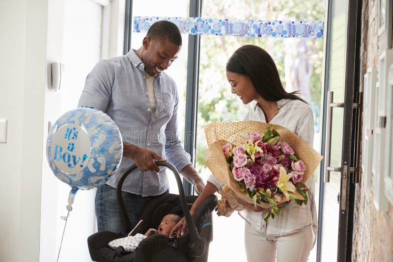 Pais que chegam em casa com o bebê recém-nascido no banco de carro imagens de stock