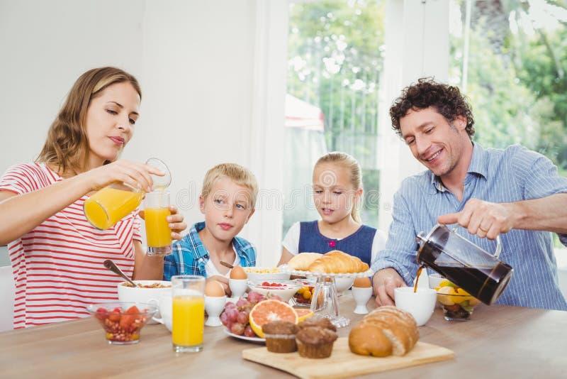 Pais que comem o café da manhã com filho e filha imagem de stock royalty free