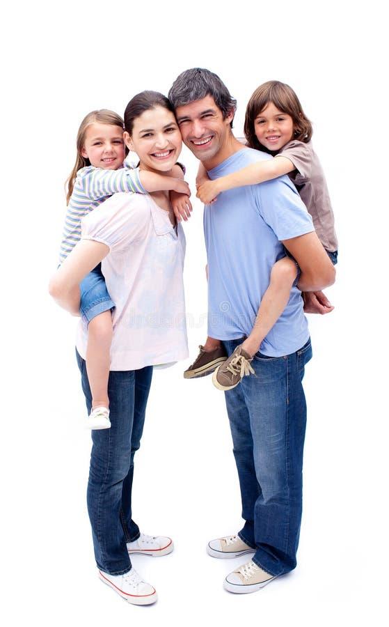 Pais que dão a suas crianças um passeio do sobreposto imagens de stock royalty free