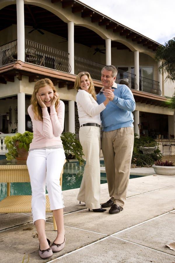 Pais que dançam atrás da filha adolescente divertida imagens de stock royalty free