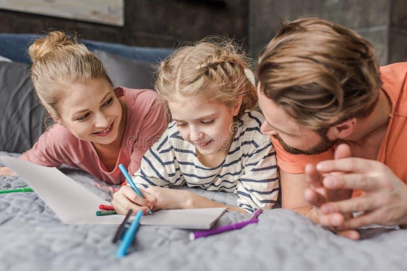 Pais que encontram-se na cama e que olham o desenho de sorriso da filha imagens de stock
