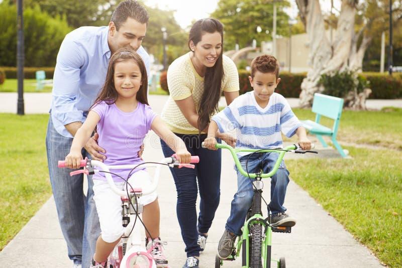 Pais que ensinam crianças montar bicicletas no parque imagens de stock