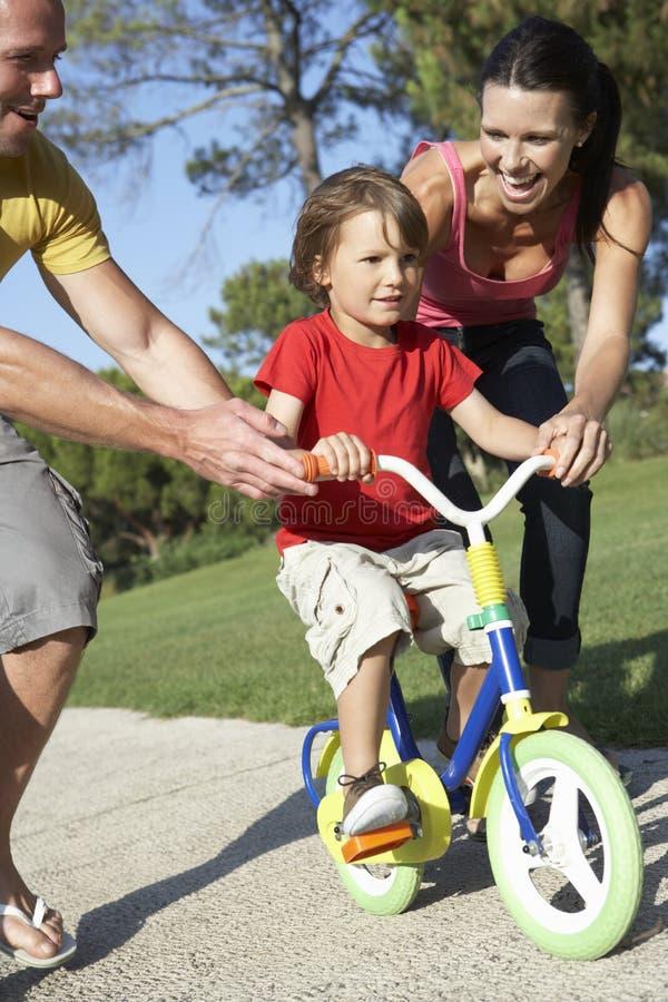 Pais que ensinam o filho montar a bicicleta no parque fotografia de stock