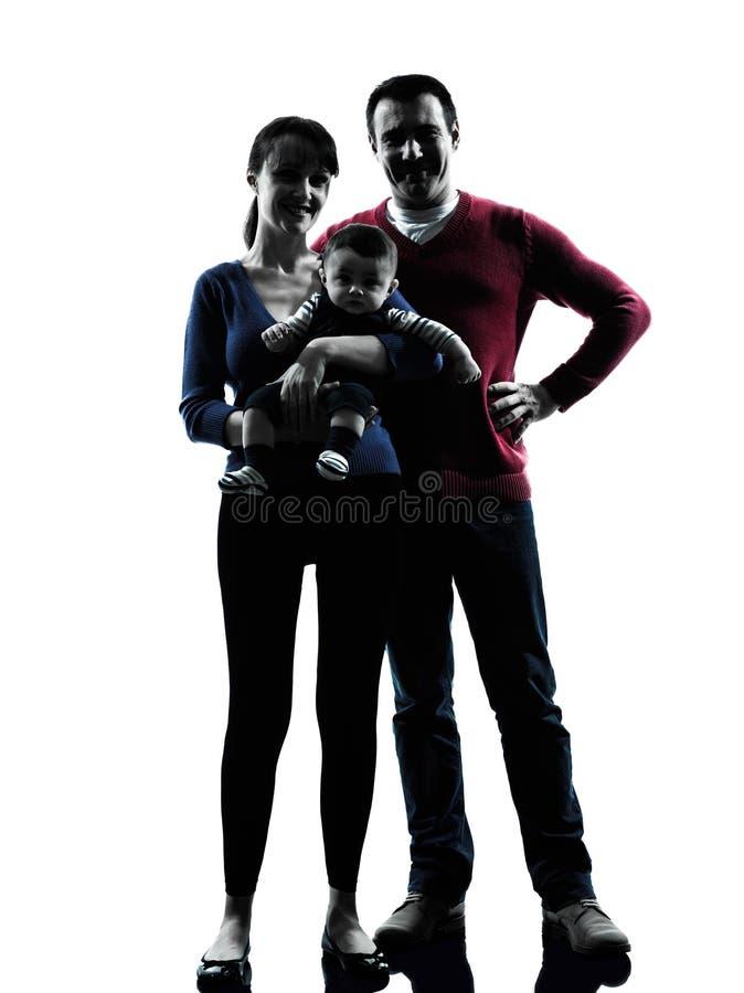 Pais que estão com silhueta do bebê imagens de stock