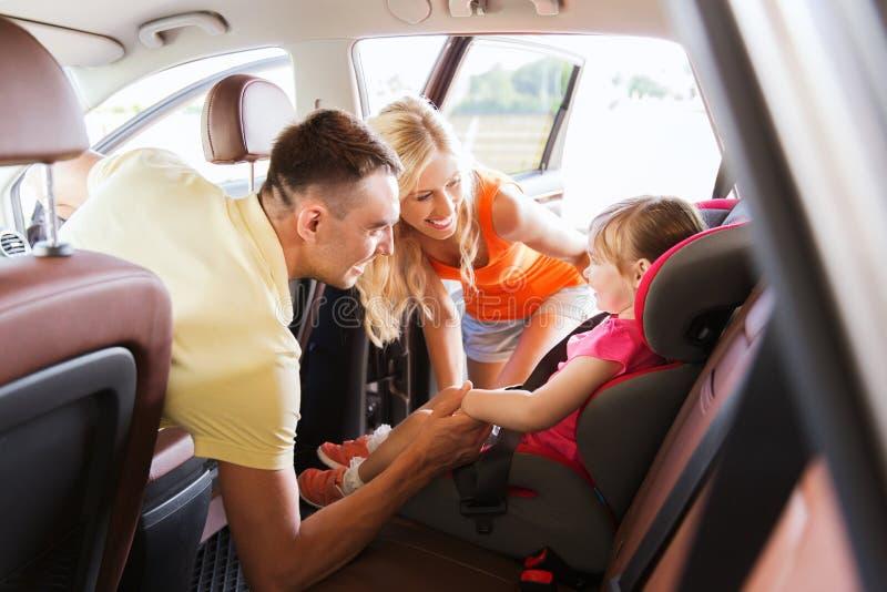 Pais que falam à menina no banco de carro do bebê imagens de stock royalty free
