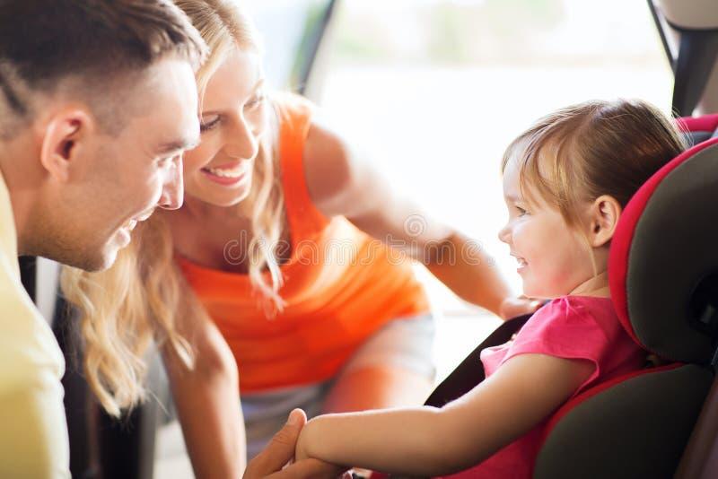 Pais que falam à menina no banco de carro do bebê foto de stock