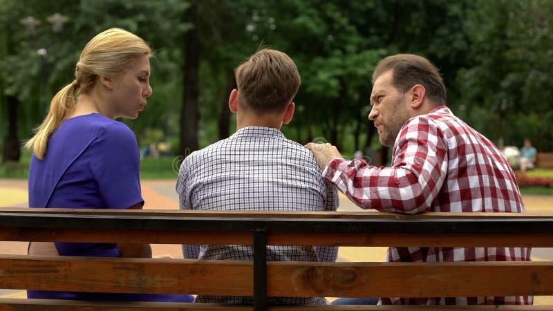 Pais que falam com o filho no banco no parque, apoio adolescente a tempo do problema fotografia de stock royalty free