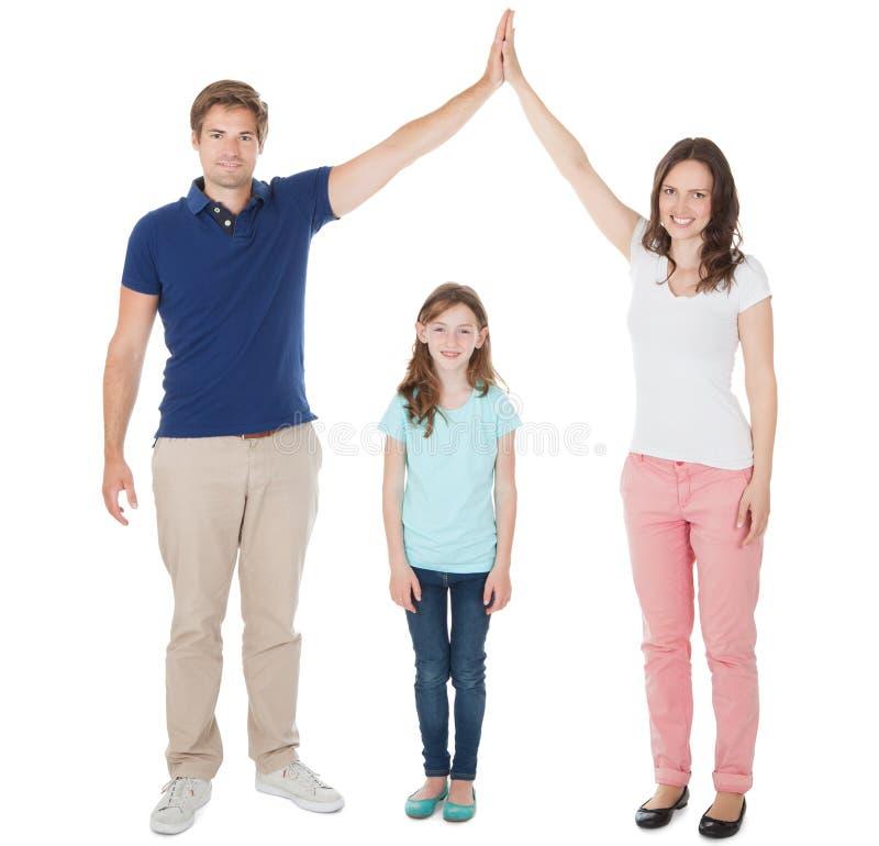 Pais que formam a forma do telhado da casa acima da filha imagem de stock