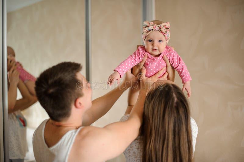 Pais que guardam sua filha pequena no romper cor-de-rosa acima em t foto de stock