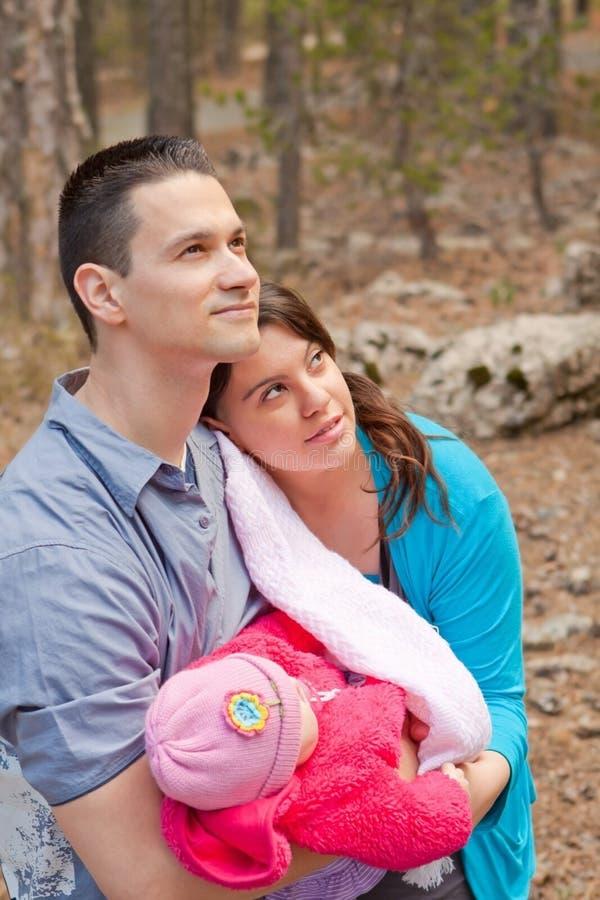 Pais que guardaram o bebê e que olham acima foto de stock