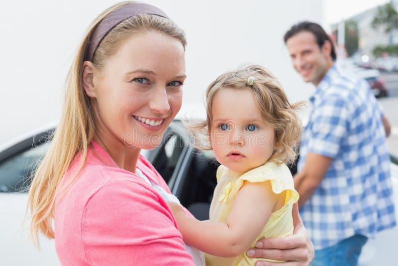 Pais que levam o bebê e o seu banco de carro fotografia de stock royalty free