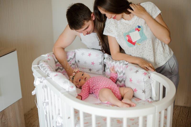 Pais que olham em sua filha feliz pequena no romper cor-de-rosa na cama foto de stock royalty free