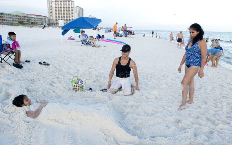 Pais que olham sua filha depois que a esculpiram em uma sereia na areia fotos de stock