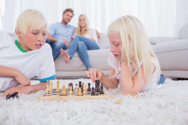 Pais que olham suas crianças que jogam a xadrez fotos de stock royalty free