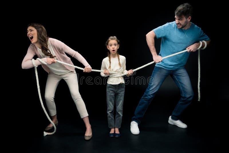 Pais que puxam sobre a filha chocada com corda, fotos de stock