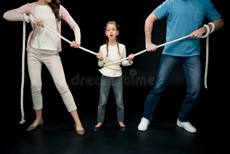 Pais que puxam sobre a filha chocada com corda imagem de stock royalty free