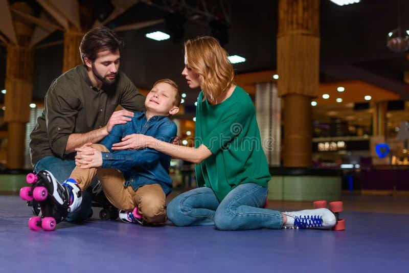 pais que satisfazem o filho de grito em patins de rolo imagens de stock