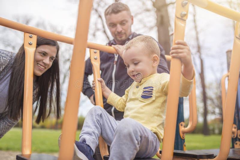 Pais que têm o divertimento com sua criança no campo de jogos do parque imagens de stock