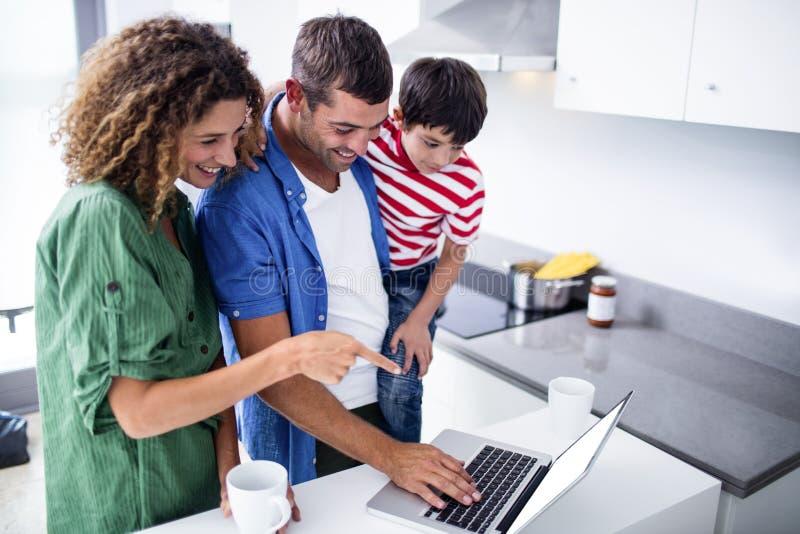 Pais que usam o portátil com o filho na cozinha fotografia de stock