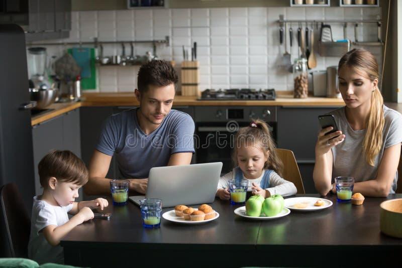Pais que usam o portátil e os smartphones que comem o café da manhã com criança fotografia de stock