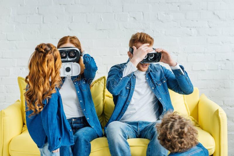 Pais que vestem os vidros 3d ao sentar-se no sofá com suas crianças imagem de stock