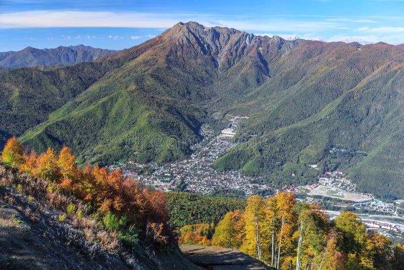Paisagem aérea ensolarada cênico da montanha do céu azul do outono da vila de Krasnaya Polyana em Sochi, Rússia com pico de Achis foto de stock royalty free