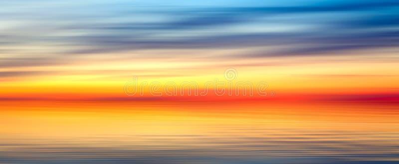 Paisagem abstrata azul amarela vermelha brilhante agradável do panorama do fundo da textura do borrão com lago do por do sol fotos de stock royalty free