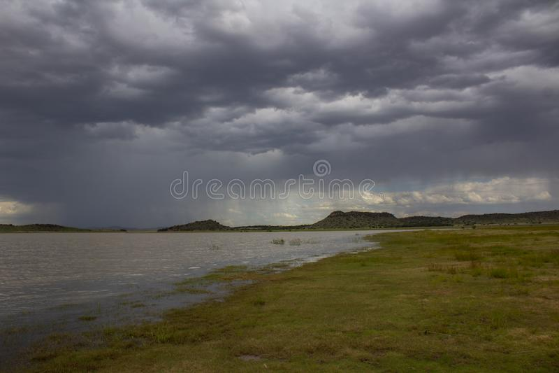 Paisagem africana - represa de Rustfontein em África do Sul e a planície na represa antes da tempestade foto de stock royalty free