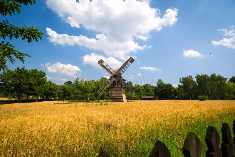 Paisagem agrícola do verão com moinho de vento velho imagens de stock royalty free