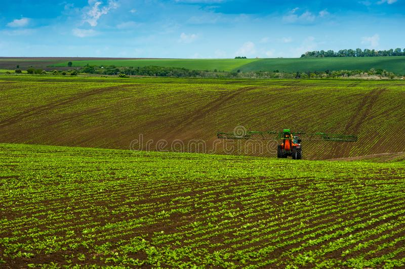 Paisagem agrícola dos montes com pulverização do trator fotos de stock