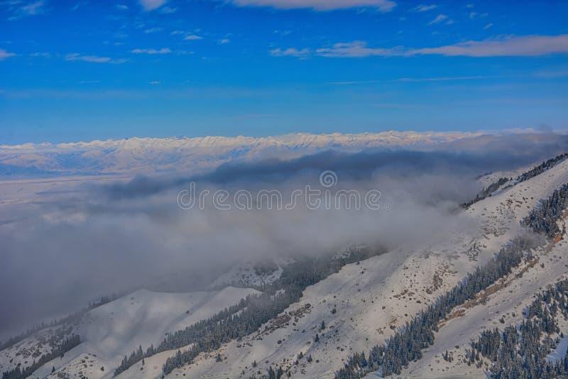 Paisagem alpina cênico com névoa sob montanhas, floresta e o céu azul Parque nacional de Quirguizistão imagens de stock royalty free