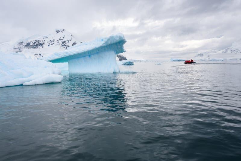 Paisagem antártica dramática no porto de Paradise, a Antártica, com iceberg esculturais e uma jangada inflável pequena que cruza  imagem de stock royalty free