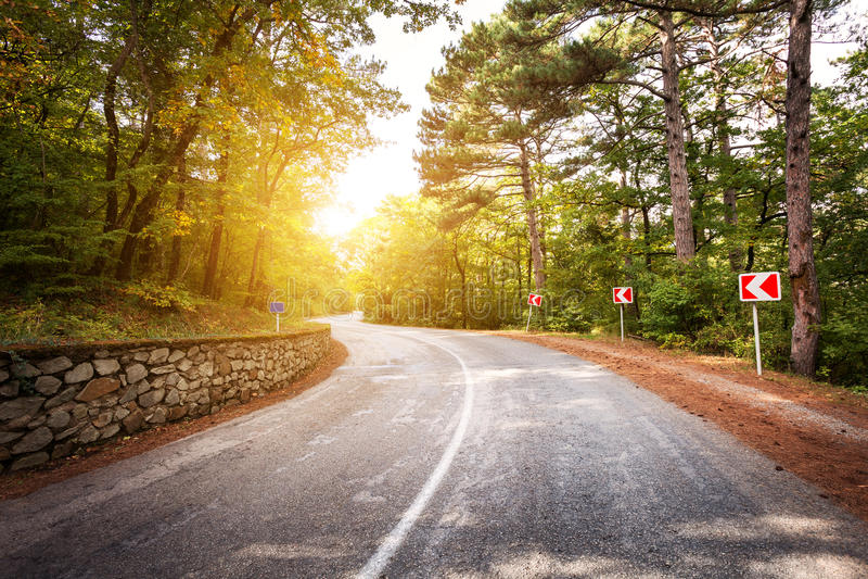 Paisagem bonita com estrada asfaltada, a floresta verde e o sinal de estrada no nascer do sol colorido no verão Montanhas crimean foto de stock